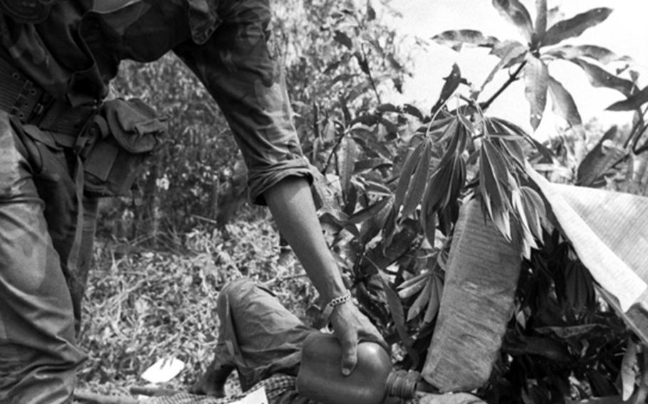 A South Vietnamese marine gives a prisoner a drink of water.
