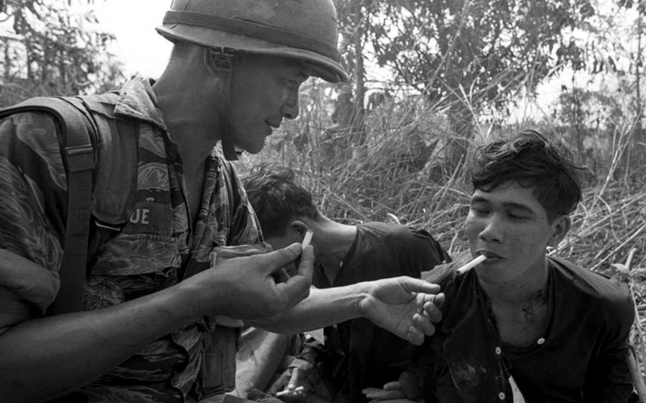 A South Vietnamese marine lights a cigarette for a Viet Cong prisoner.