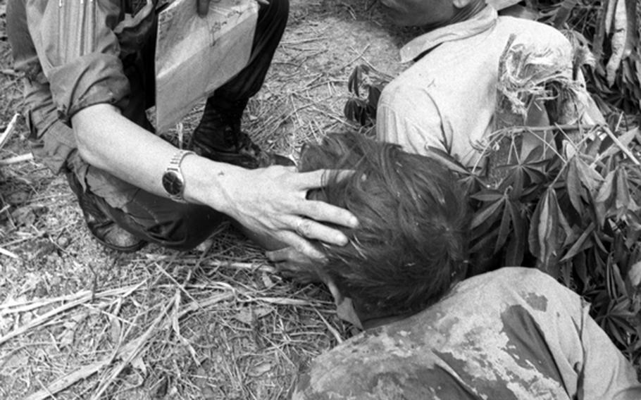A South Vietnamese marine checks the condition of Viet Cong prisoners awaiting a move to an interrogation center.