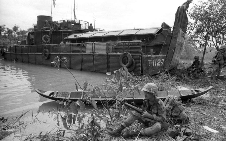 A marine from the 5th Vietnamese Marine Division poses next to a small Viet Cong boat on the banks of the My Tho River, 65 miles southwest of Saigon. In the background is an armored troop carrier.