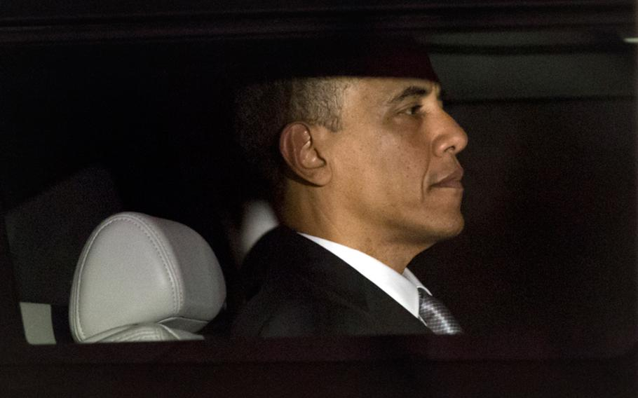 President Barack Obama is seen through the window of a limo as he returns to the White House for the first time since his victory on election day, in Washington, Wednesday, Nov. 7, 2012.