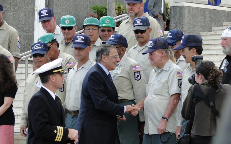 Defense Secretary Leon Panetta shakes hands with the men who work at the National Memorial Cemetery of the Pacific in Hawaii. Panetta paid tribute to the nation's veterans during a Veterans Day observance before embarking on a trip to several nations in the Pacific.