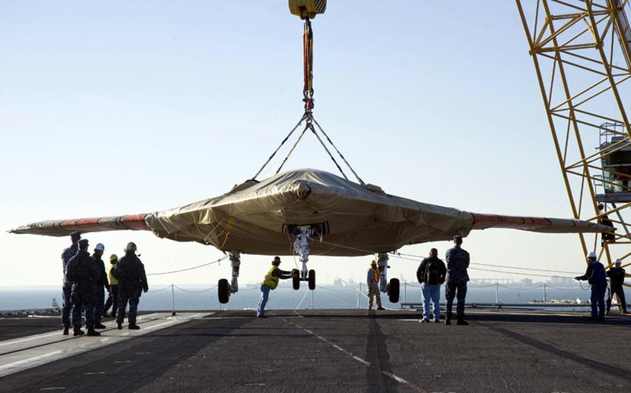 U.S. Navy Sailors assist in loading the X-47B Unmanned Combat Air System (UCAS) demonstrator aboard the aircraft carrier USS Harry S. Truman (CVN 75) on Nov. 26, 2012.