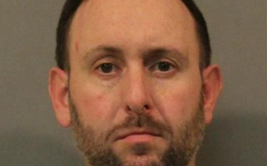 Timothy R. Thomas, a police officer with the Department of Veterans affairs, is charged with murdering Navy veteran Nicholas Lile, 42, on Jan. 3 while drinking with their spouses and friends in the basement of Liles' Lowell, Ind. home.