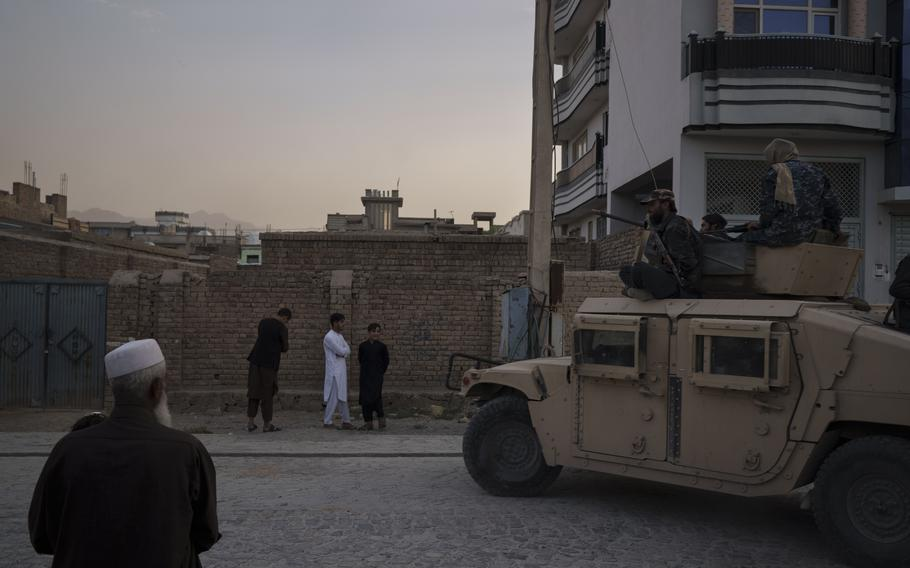 Afghans watch as Taliban fighters ride atop a humvee after detaining four men who got involved in a street fight in Kabul, Afghanistan, Tuesday, Sept. 21, 2021.