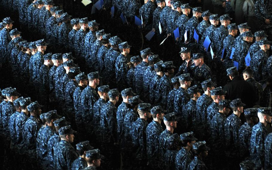 """Newly promoted petty officers stand in formation in thier NYCO uniforms aboard the USS George Washington during a frocking ceremony Dec. 7, 2012. The nylon-and-cotton uniforms worn by sailors on ships and at bases """"will burn robustly,"""" and turn into a """"sticky molten material,"""" according to a test conducted by the Navy Clothing and Textile Research Facility."""