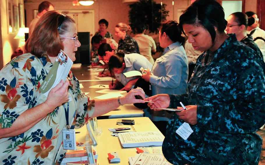 Janise Wilcox, a Tricare representative, hands out information packets on Tricare to a sailor at a Naval Station Norfolk pregnancy seminar in June, 2009. The seminar was open to all female and male sailors who have either had children or are contemplating starting families.