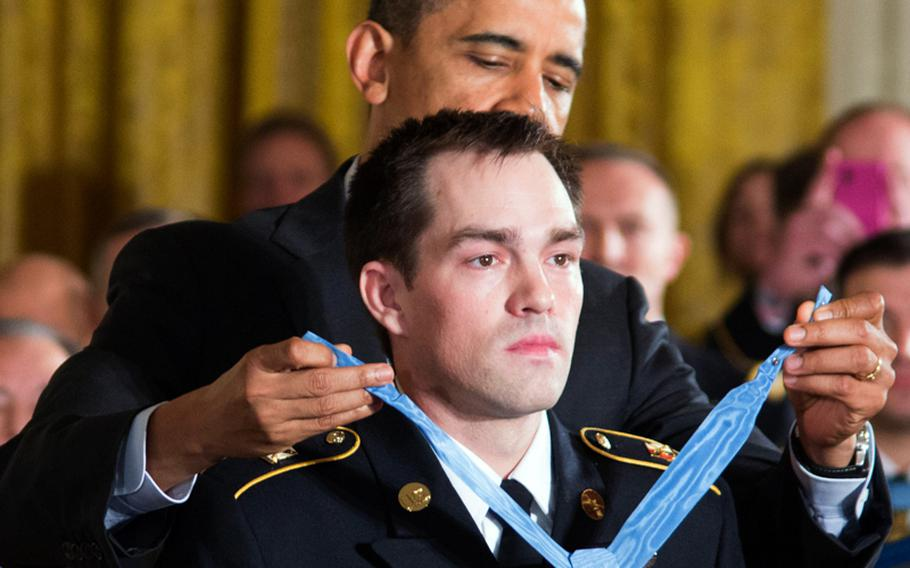 President Barack Obama presents the Medal of Honor to former Army Staff Sgt. Clinton Romesha Monday, Feb, 11, 2013, at the White House.