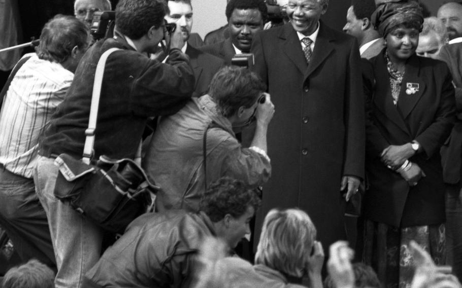 Photographers focus in on Nelson Mandela and his wife, Winnie, as they arrive at a rally in Bonn in June, 1990.