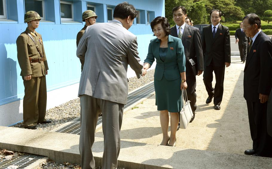 """In this photo released by the South Korean Unification Ministry, Kim Song Hye, center, the head of North Korea's delegation, shakes hands with an unidentified South Korean officer before crossing a military demarcation line, which has separated the two Koreas since the Korean War, for a meeting with South Korean delegates at Panmunjom in Paju, north of Seoul, South Korea, Sunday, June 9, 2013. Government delegates from North and South Korea began preparatory talks Sunday at the """"truce village"""" on their heavily armed border aimed at setting ground rules for a higher-level discussion on easing animosity and restoring stalled rapprochement projects."""