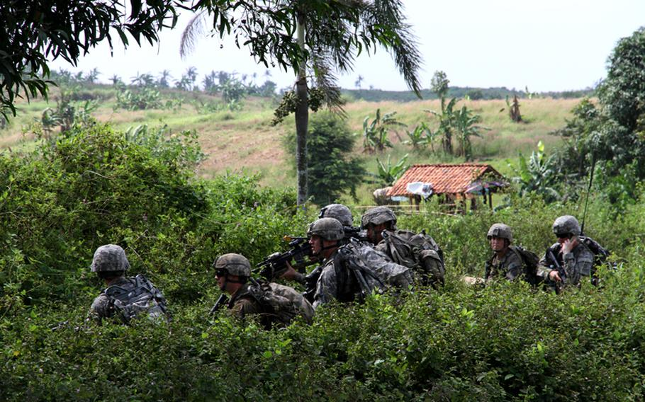 Paratroopers of the 82nd Airborne Division hunker down before a mock assault on a row of abandoned buildings, June 18, 2013. The UN peacekeeping scenario was part of the Garuda Shield exercise going on in Indonesia.