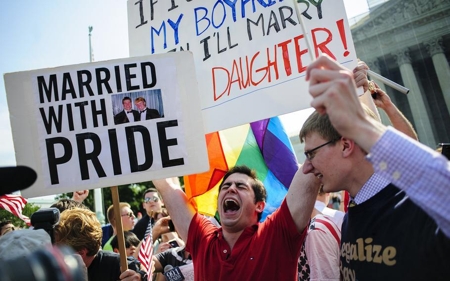 David Baker, 24, center, of Phoenix, Arizona, celebrates outside the Supreme Court after hearing that the Court struck down the Defense of Marriage Act, Wednesday, June 26, 2013, in Washington, D.C.