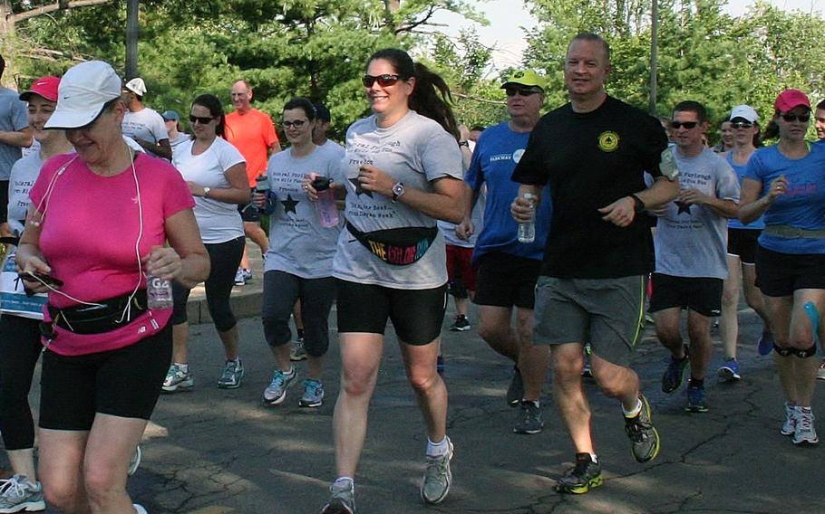 DOD civilian employee Christine Smith (center) was one of nearly 50 people who set out across the street from the Pentagon on a five mile run for furloughed defense civilians on July 8, 2013. Organizers cut the run to four miles mid-race to symbolize a 20 percent pay loss.