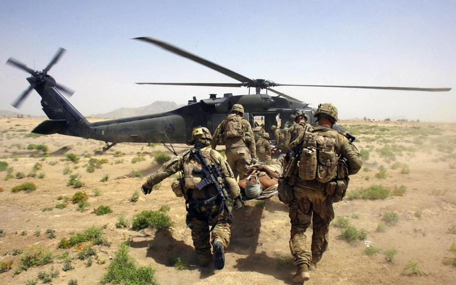 U.S. troops carry a wounded soldier, injured by an improvised explosive device in Afghanistan, to a helicopter on June, 15, 2011.