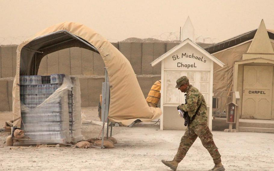 A U.S. Army soldier walks past St. Michael's Chapel during a dust storm at Forward Operating Base Shank, Logar province, Afghanistan, March 19, 2012.