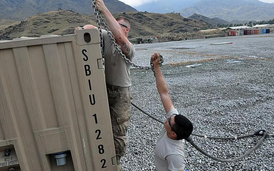 Pfc. Ty Cummings, left, and Sgt. Lucas Strozak, 1st Brigade Combat Team, 101st Airborne Division,  prepare a shipping container June 15 to be picked up by helicopter at Forward Operating Base Joyce in eastern Afghanistan.