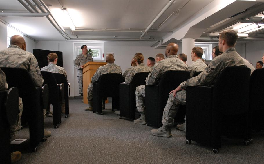 Staff members with the Air Force Deployment Transition Center at Ramstein Air Base, Germany, along with guests listen to Master Sgt. Corey Hancock talk about the history of the center during a ceremony Tuesday. The center was celebrating its third-year anniversay.