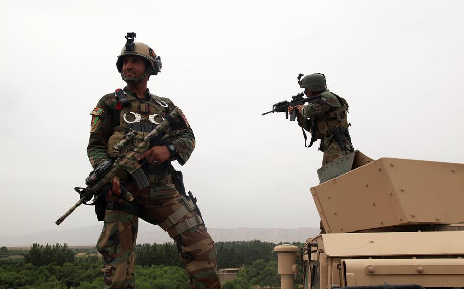 In this file photo from June 3, 2013, 2 Afghan National Army special forces soldiers pull security outside of a combat outpost in Chahar Darreh district, Kunduz province, Afghanistan.