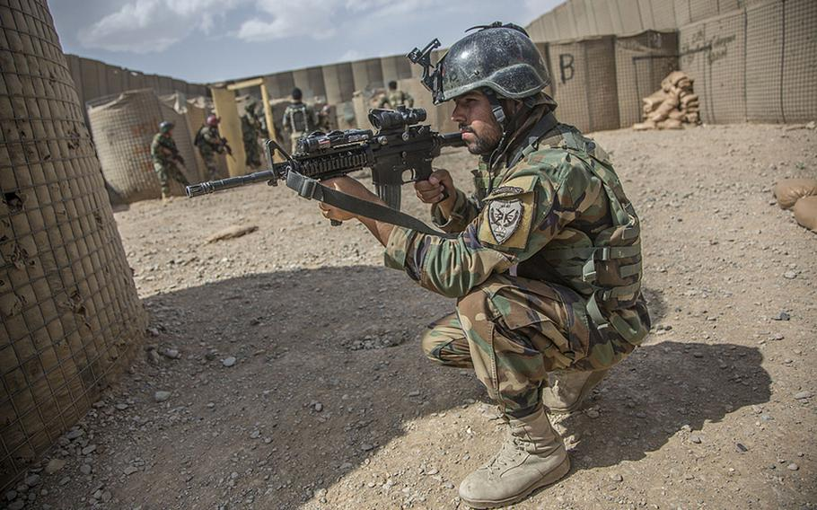 An Afghan Commando pulls rear security while others clear a compound during close quarters combat training in Washer district, Helmand province, Afghanistan, May 8, 2013.