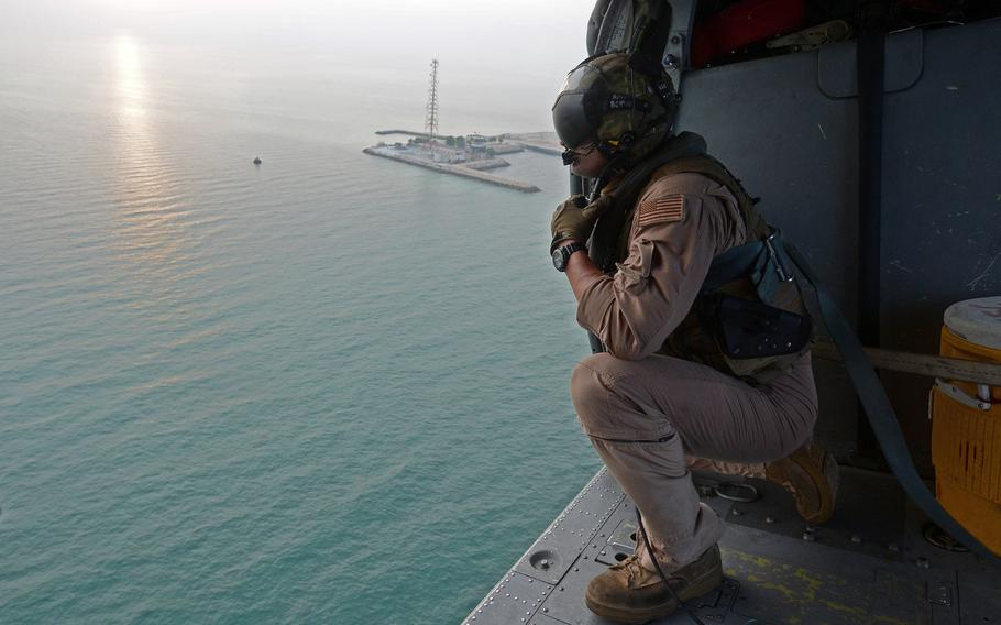 A sailor with Helicopter Sea Combat Squadron 26 looks out an MH-60S Sea Hawk helicopter while on a search and rescue training operation. Attached to Commander, Task Force 53, HSC-26's Det. 1 provides combat logistics and search and rescue capability throughout the U.S. 5th Fleet area of responsibility.