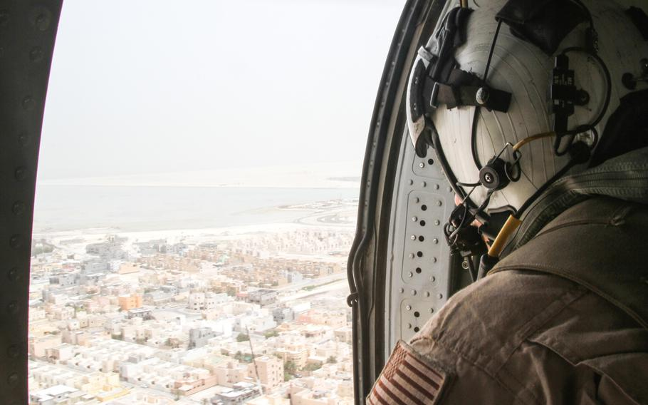 Petty Officer 3rd Class Travis Calvan, an air crewman, looks out from an MH-60 helicopter flying over Bahrain, May 21, 2013.