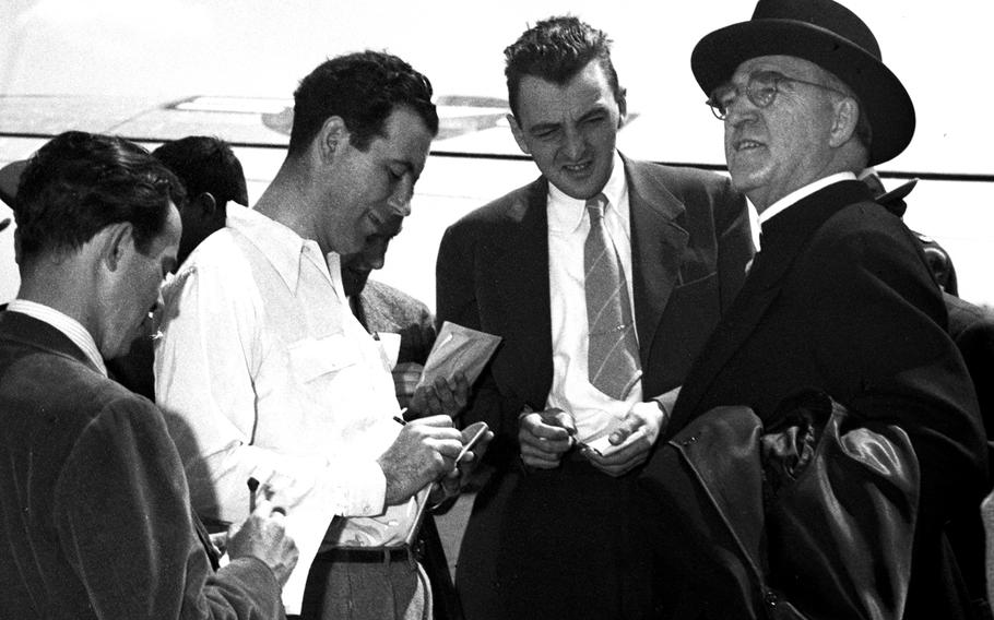 Msgr. Edward J. Flanagan, founder of the famous Boys Town children's home in Nebraska, talks with reporters at the Rhein-Main airport in May, 1948.