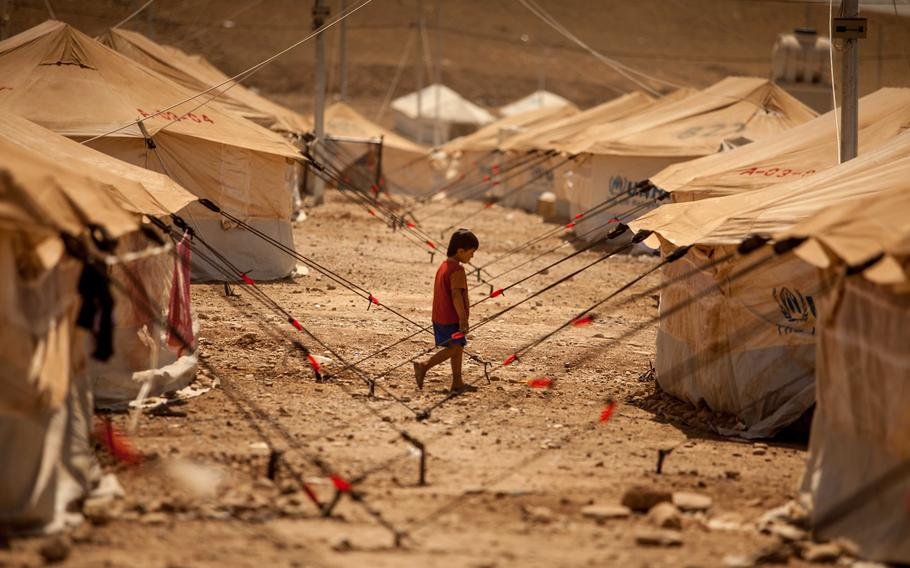 A  child walks between dusty tents to look for his family in the Quru Gusik refugee camp set up near the border with Syria, August 24, 2013. United Nations aid agencies say the number of children fleeing Syria has now reached one million.