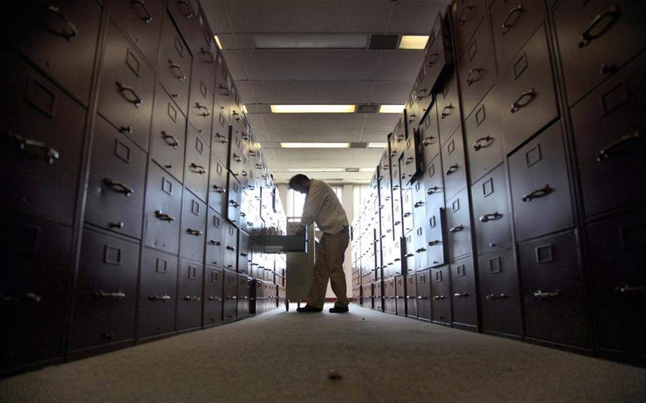 A claims assistant files veterans cases into enormous rows of filing cabinets at the U.S. Department of Veterans Affairs in Los Angeles on December 5, 2012.