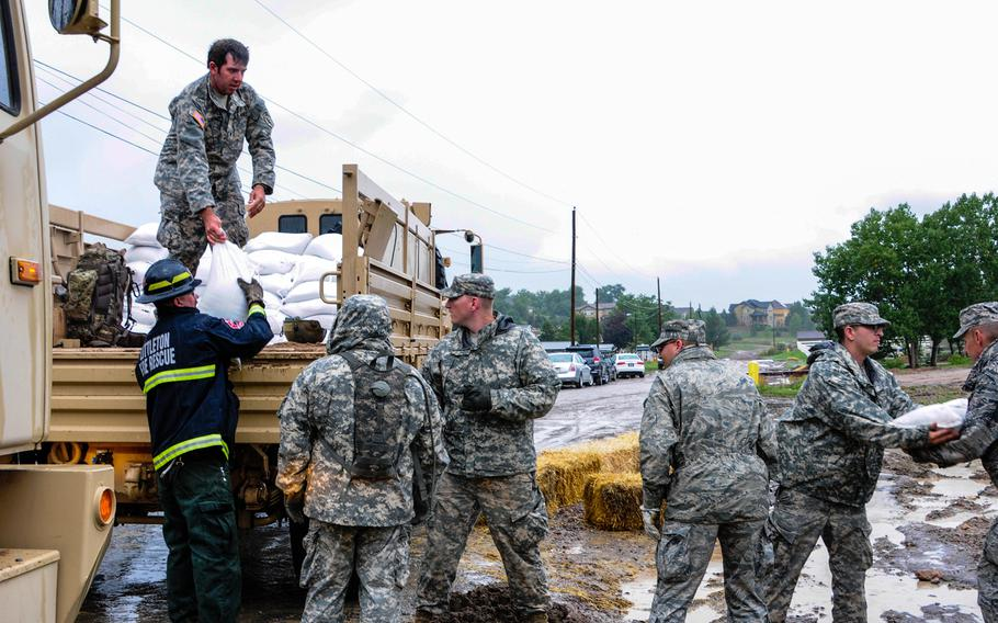 U.S. soldiers and airmen from the Colorado National Guard, along with members of civilian emergency response agencies, fill sandbags at the Arvada Fire Protection District Training Center in Arvada, Colo., to help mitigate flooding in the area, Sept. 15, 2013.