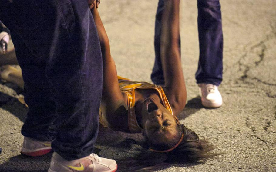A women becomes emotional Thursday, Sept. 19, 2013, near the scene of a shooting at Cornell Square Park in Chicago's Back of the Yard neighborhood that left multiple victims wounded, including a 3-year-old boy.