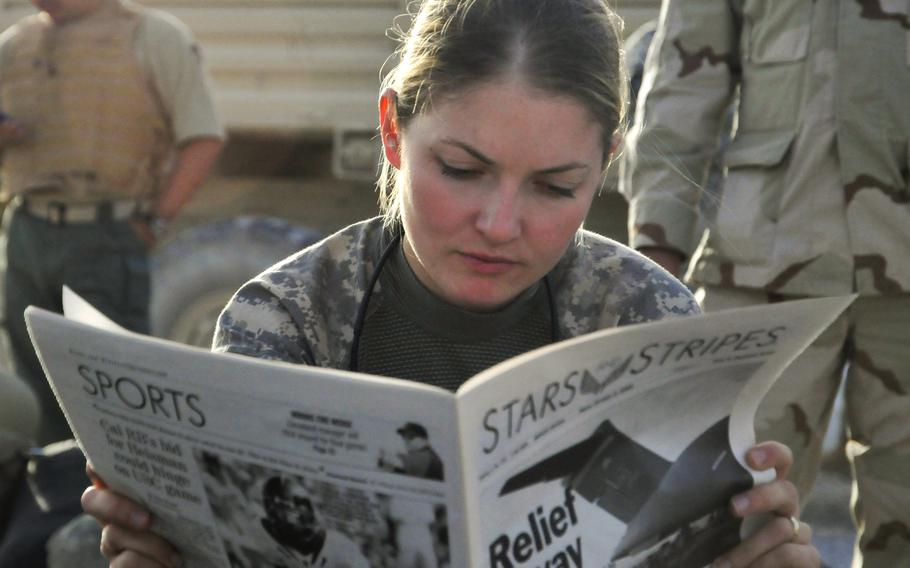 In a 2009 file photo, First Lt. Tracy Tyson from Seattle, Wash., assigned to the 5th Brigade 2nd Infantry Division reads Stars and Stripes in Kandahar Airfield, Afghanistan, while waiting for a flight to Forward Observation Base Wolverine.