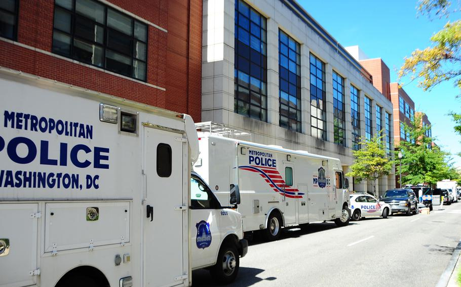 Washington Metropolitan Police Department vehicles are parked near the Naval Sea Systems Command headquarters building at the Washington Navy Yard on Sept. 18, 2013. The Navy awarded a $6.4 million contract to make safety repairs and assessments on whether to keep the building. On Sept. 16, former sailor Aaron Alexis shot and killed 12 people in the building.