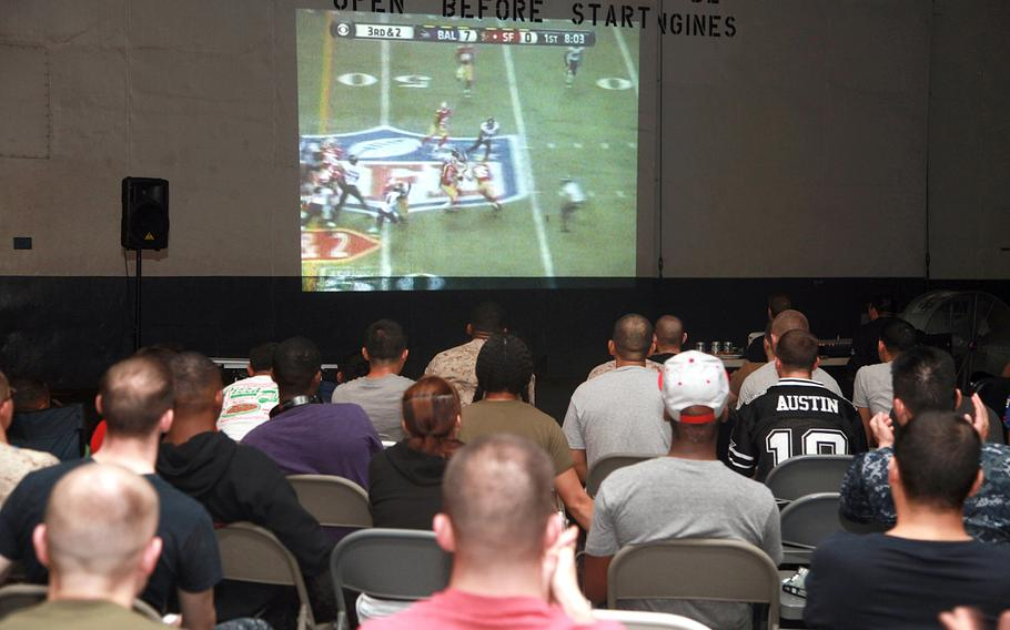 Marines and sailors with the 15th Marine Expeditionary Unit and Peleliu Amphibious Ready Group watch Super Bowl XLVII during the Super Bowl party held in the hangar bay of the USS Peleliu, on Feb. 4, 2013.