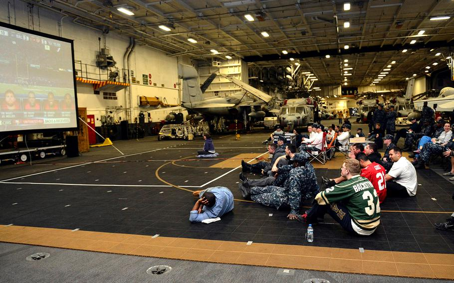 Sailors stationed aboard the aircraft carrier USS John C. Stennis watch the Super Bowl in hangar bay two on Feb. 04, 2013.