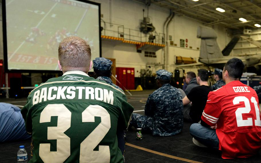 Sailors stationed aboard the aircraft carrier USS John C. Stennis watch the Super Bowl in hangar bay two on Feb. 4, 2013.