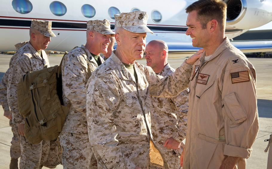 Gen. James F. Amos, commandant of the Marine Corps, exchanges greetings with Navy Capt. Christopher Dennis, commanding officer of Naval Air Station Sigonella, Italy, on June 15, 2013.