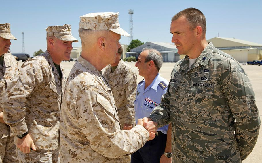 Gen. James F. Amos, commandant of the Marine Corps, exchanges greetings with an Air Force lieutenant colonel after arriving at Moron Air Base, Spain, on June 15, 2013, to meet with Marines and Sailors assigned to Special-Purpose Marine Air-Ground Task Force Africa 13.