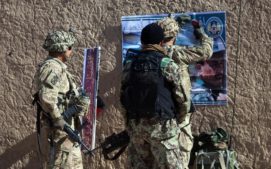 U.S. troops and an Afghan National Army soldier hang a poster on a wall at the Usmankhel Village, Kandahar province, Afghanistan, Dec. 18, 2011.