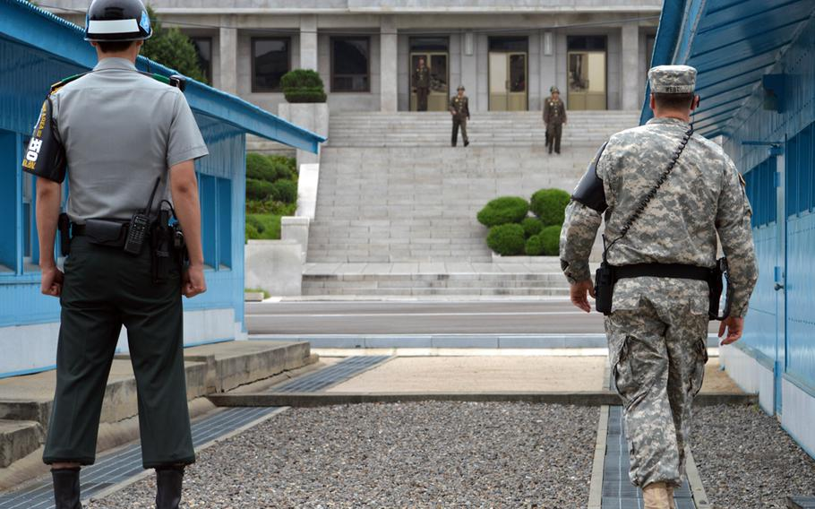 A U.S. soldier walks forward while a South Korean soldier stands ready as three North Korean soldiers approach the demarcation line at the Joint Security Area, South Korea, July 27, 2013. Both U.S. and South Korean soldiers are United Nations Command Security Battalion members.