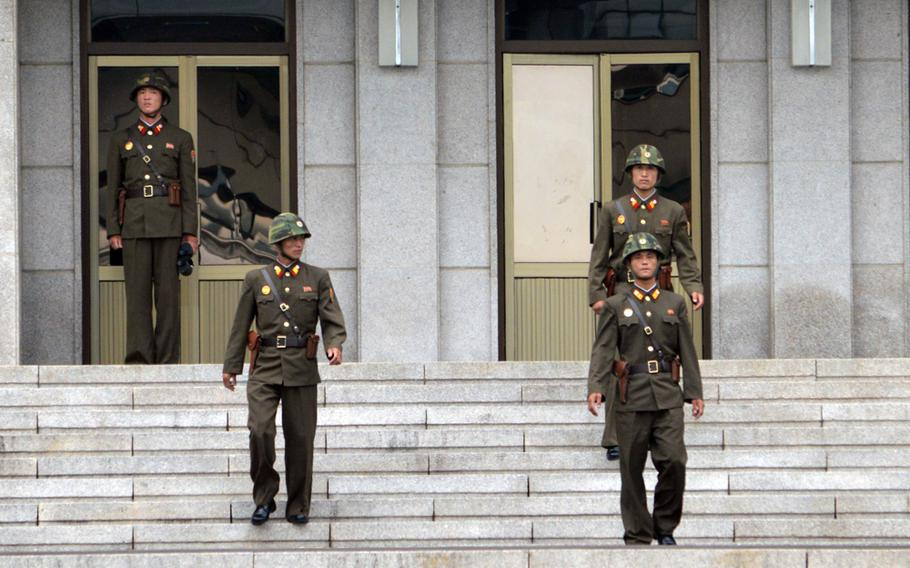 North Korean soldiers walk down the stairs of the Panmungak building at the Joint Security Area, North Korea, July 27, 2013. North Korean soldiers regularly venture out of the building to observe their South Korean counterparts.