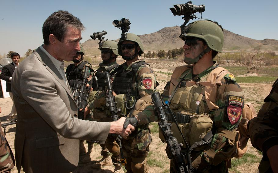 NATO Secretary General Anders Fogh Rasmussen shakes hands with an Afghan commando at Camp Morehead, Afghanistan, April 12, 2012.