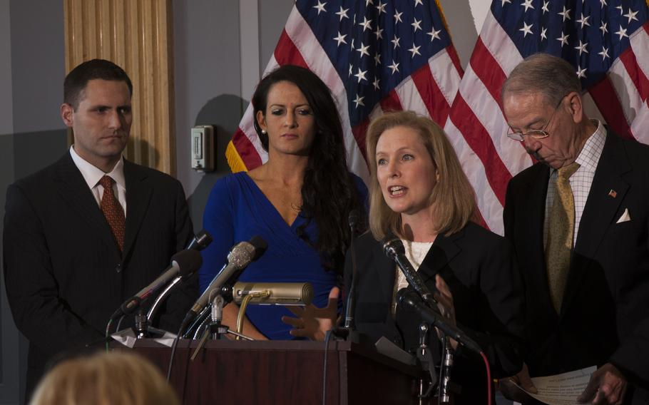 Sen. Kirsten Gillibrand (D-NY) calls for military sexual assault cases to be removed from the military chain of command on on Nov. 6, 2013 in Washington, D.C. Behind her are Ariana Klay, a former Marine officer who was sexually assaulted and her husband, Ben Klay (left), a former Marine, and Sen. Chuck Grassley (R-Iowa.)
