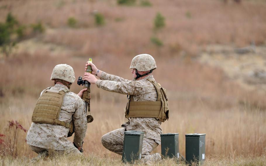 Sgt. Garrett Dennard, an instructor with the Infantry Officer Course at Marine Corps Base Quantico, Va., loads a 60mm mortar round during a demonstration of the new Fire Control Unit sight on Tuesday. In addition to improving accuracy, officials believe the sight will save lives and cut costs over the duration of its use.