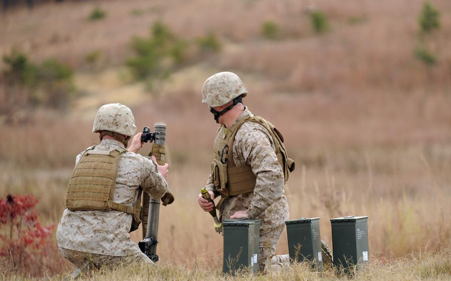Cpl. Justin Auclair, assigned to the Warfighter Instructor Company, makes final adjustments to the Office of Naval Research's new Fire Control Unit 60mm Mortar sight during a demonstration Tuesday at Marine Corps Base Quantico, Va.