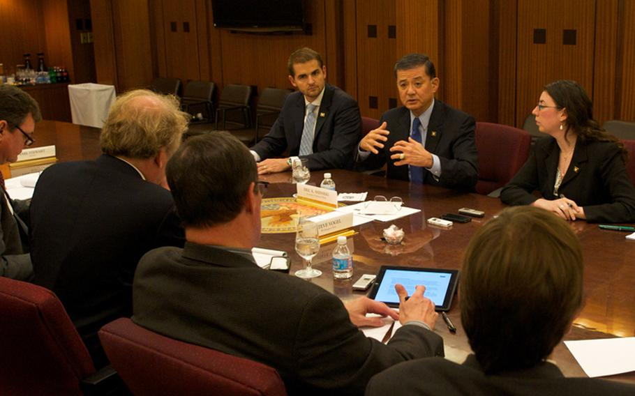 Veterans Affairs Secretary Eric Shinseki, 5th from left, meets with reporters Thursday, Nov. 7, 2013, to discuss progress made in clearing a backlog of disability claims.