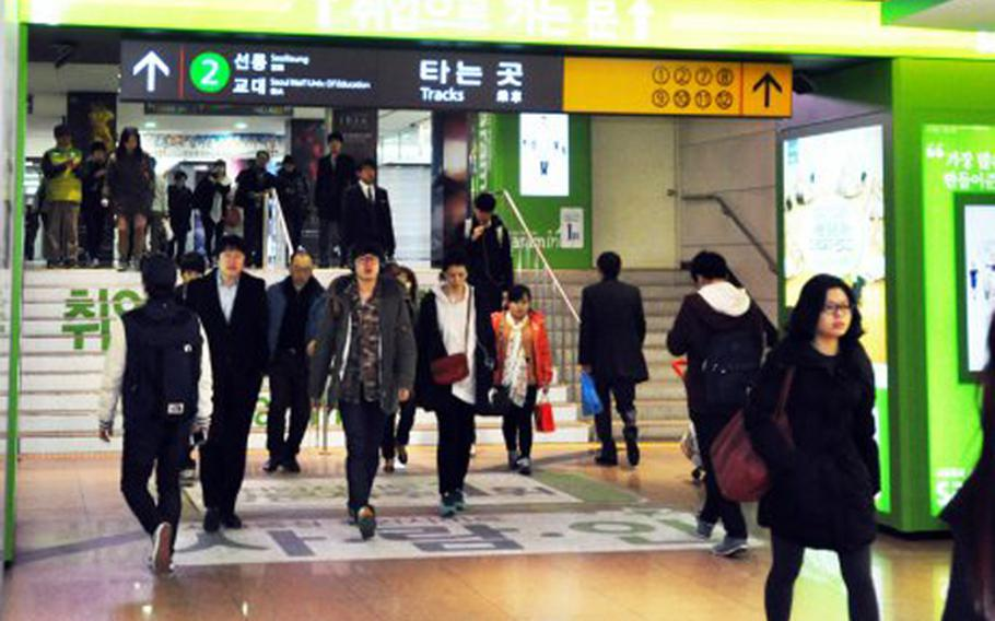 Commuters travel through a crowded Seoul, South Korea, subway station in February 2013.
