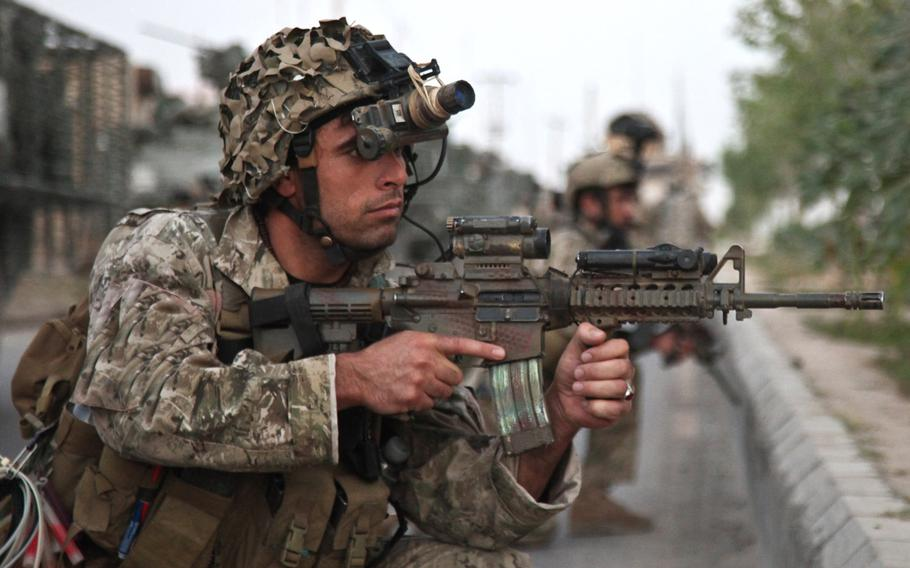 An Afghan security force member provides security during an operation in search of a Taliban facilitator in Dand district, Kandahar province, Afghanistan, May 23, 2013.
