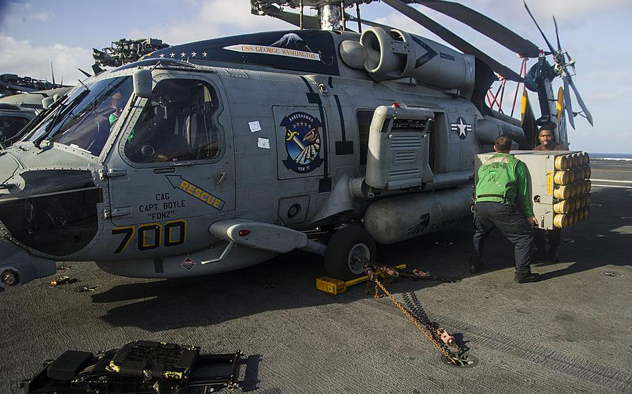 Sailors assigned to the Saberhawks of Helicopter Maritime Strike Squadron remove equipment from an MH-60R Seahawk helicopter aboard the USS George Washington as the carrier was en route to the Republic of the Philippines on Nov. 13, 2013, to support humanitarian efforts in response to Typhoon Haiyan.