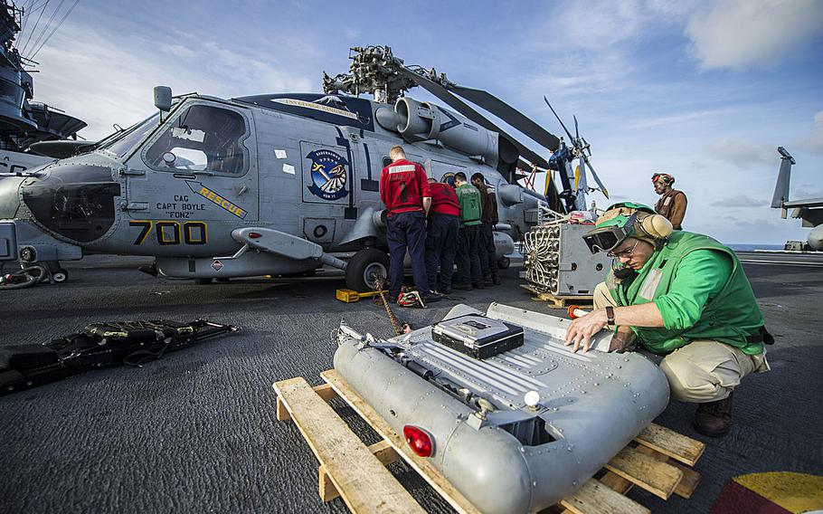 Sailors assigned to the Saberhawks of Helicopter Maritime Strike Squadron remove equipment from an MH-60R Seahawk helicopter aboard the USS George Washington as the carrier was en route to the Philippines on Nov. 13, 2013, to support humanitarian efforts in response to Typhoon Haiyan.