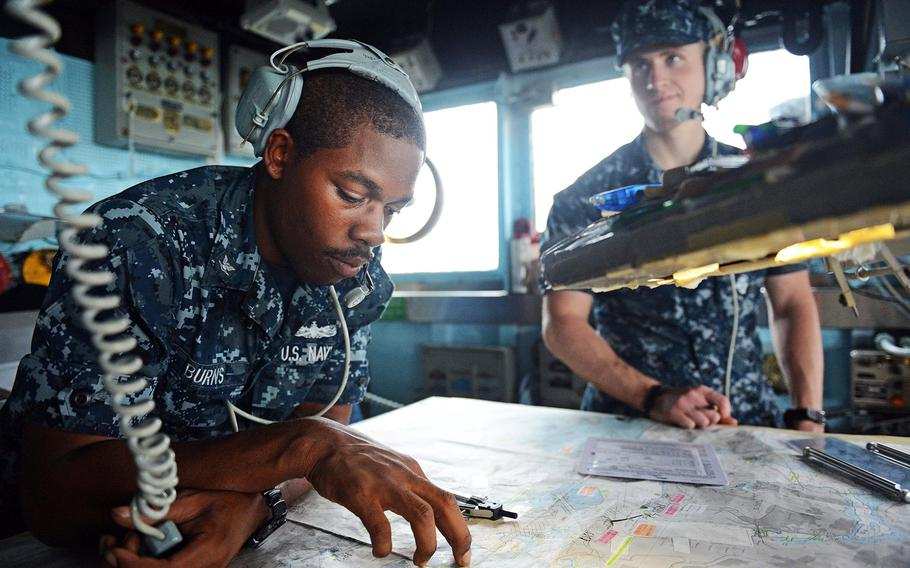 Petty Officer 3rd Class Juan Burns, assigned to the Ticonderoga-class guided-missile cruiser USS Antietam, reviews navigational charts in the bridge wing as the ship prepares to leave the port of Hong Kong on Nov. 12, 2013.